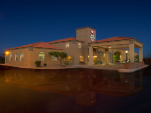 Hotel exterior at night with reflection at the Best Western PLUS Winslow Inn - Winslow, Arizona